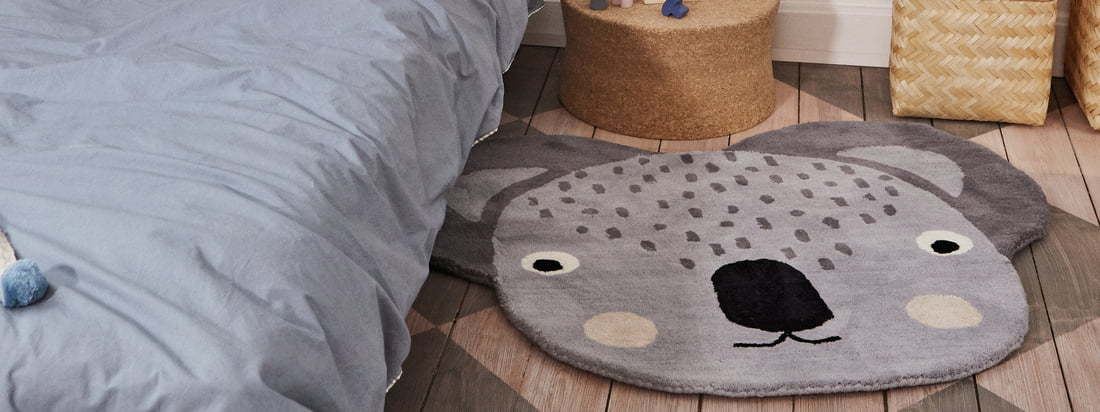 Lifestyle product image of the Koala children's carpet measuring 100 x 85 cm by OYOY. Before the bed, the carpet becomes a practical eye-catcher in the children's room.