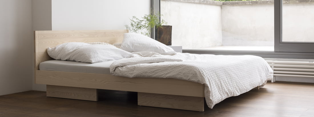Zian's bed with headboard by Objekte unserer Tage in the ambience view. Simple shapes and straight lines characterize the calm and unagitated design of the bed, which fits perfectly into any bedroom due to its reduced appearance.