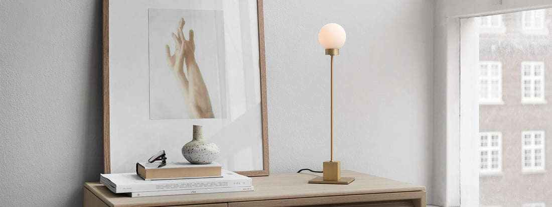 Snowball table lamp H 41 cm, brass by Northern in the ambience view. Used as a work lamp on the desk or background lighting in the living room on the sideboard, the light of the Snowball table lamp provides a cozy atmosphere in the room.