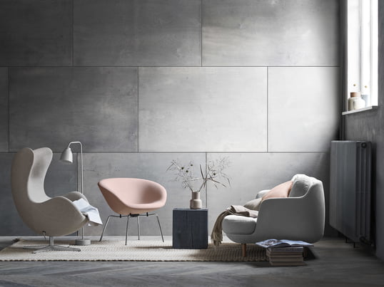 The Cosy Lune 2-seater sofa by Fritz Hansen with the matching Pot chair in soft grey and shades of pink. A modern living room ambiance in front of a grey wall.