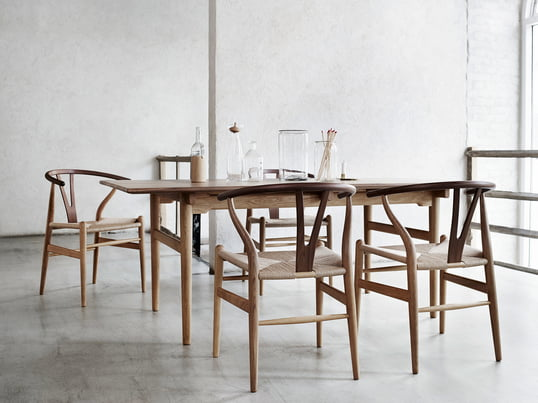 Lifestyle product image of the CH24 Wishbone Chair by Carl Hansen: The simple appearance makes it hard to guess that 100 individual steps are needed to make the chair.