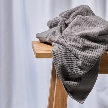 The Zone Denmark - Classic Grey Hand Towel on a Wooden Bench